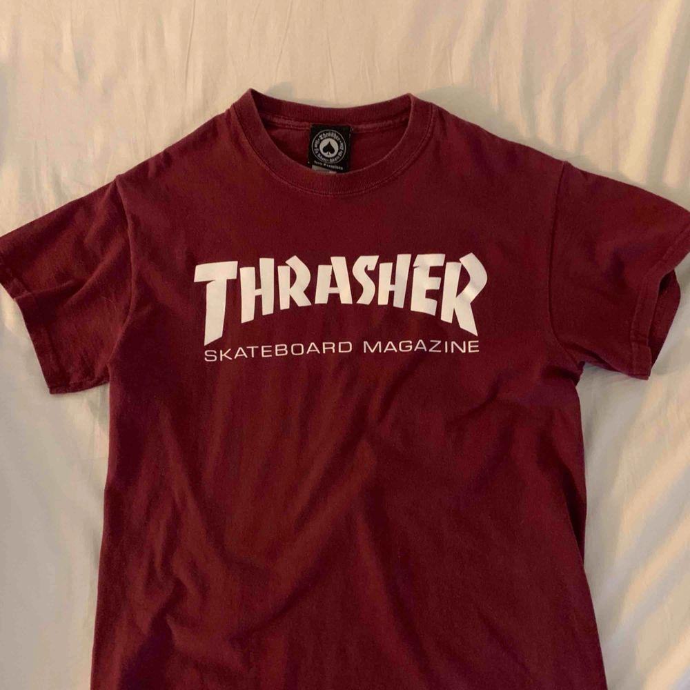 Vinröd thrasher t shirt storlek small. T-shirts.