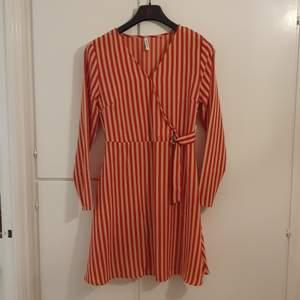 Beige och röd randig klänning med detalj i midjan.