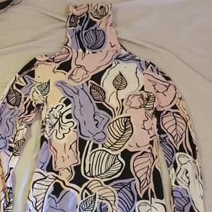 En stretchig polotröja från monki! Den är pastell rosa, vit, lila och lite svart. Blad och nakna kvinnor (krokier) på tröjan. Väldigt tunn och