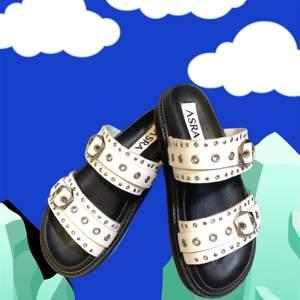 🔸 Märke: ASRA                                                            🔸 Typ: Sandaler/tofflor                                                     🔸 Material: Skinn                                                           🔸 Färg: Vit/svart/silver                                                  🔸 Skick: Oanvända, nyligen köpta                                                         🔸 Övrigt: Nypris 749 kronor