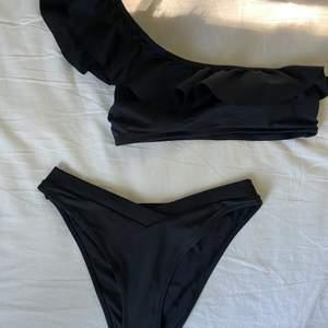En söt svart bikini med volanger från H&M. Säljer då den tyvärr var för liten för mig. Aldrig använd, endast testad. Lappen sitter på bikini toppen. Skicka gärna frågor om ni undrar något💞😊