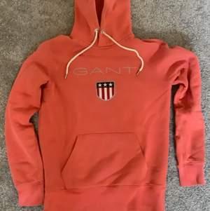 En mycket fin coral färgad gant hoodie med vita snören. Ganska tjock mysig hoodie från gant färgad som en solnedgång. Är i storleken xs är relativt använd men ändå i bra skick (9/10)
