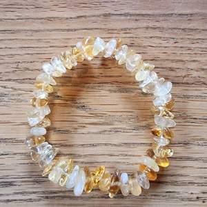 Armband med kristallpärlor av citrin.  Chipsformade stenar trädda på elastisk tråd. Ca 16 cm omkrets. Skickas i vadderat kuvert via postnord.