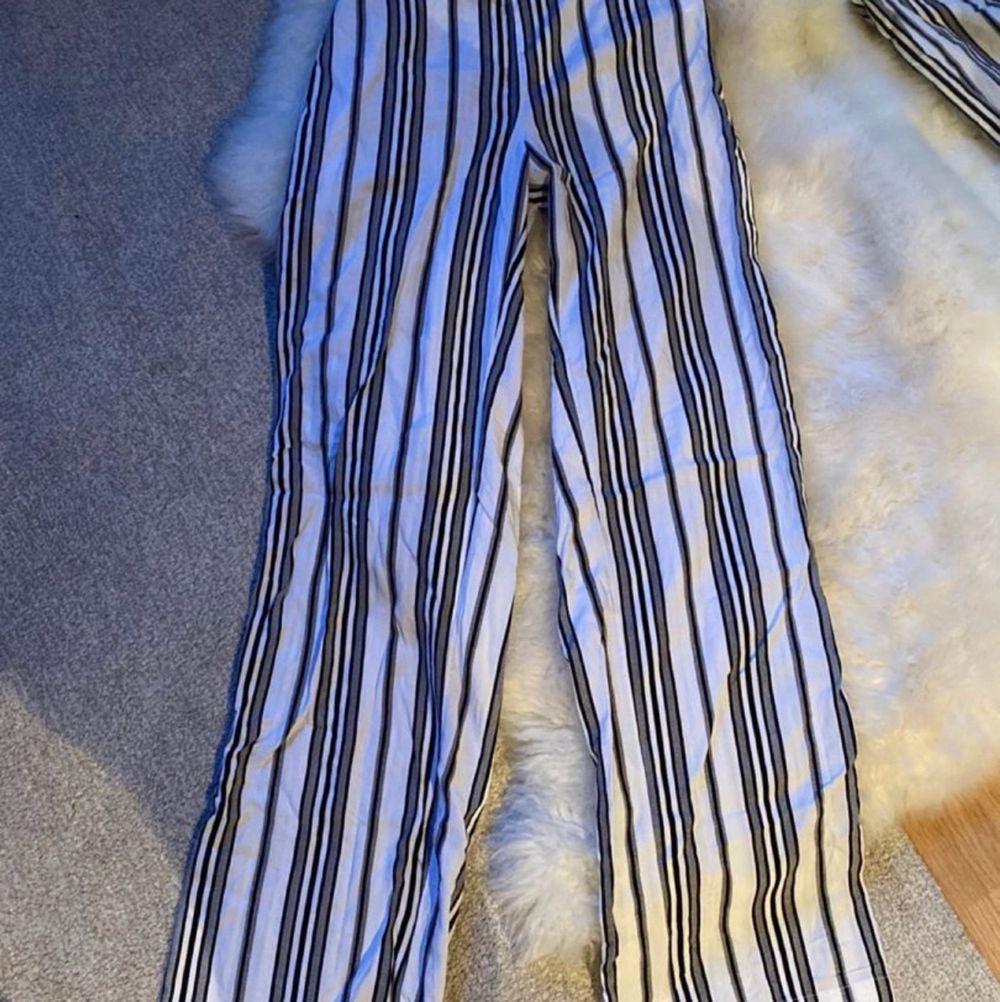 Randiga kostymbyxor/flowiga byxor i vit/grå/svart från BikBok i stl XS. Säljs oanvända för 100kr + frakt!🥰. Jeans & Byxor.