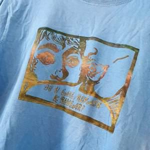 En blå t-shirt med ännu ett blandat handtryck av