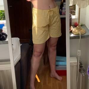 Gul och vit randiga strand shorts. Köparen står för frakten