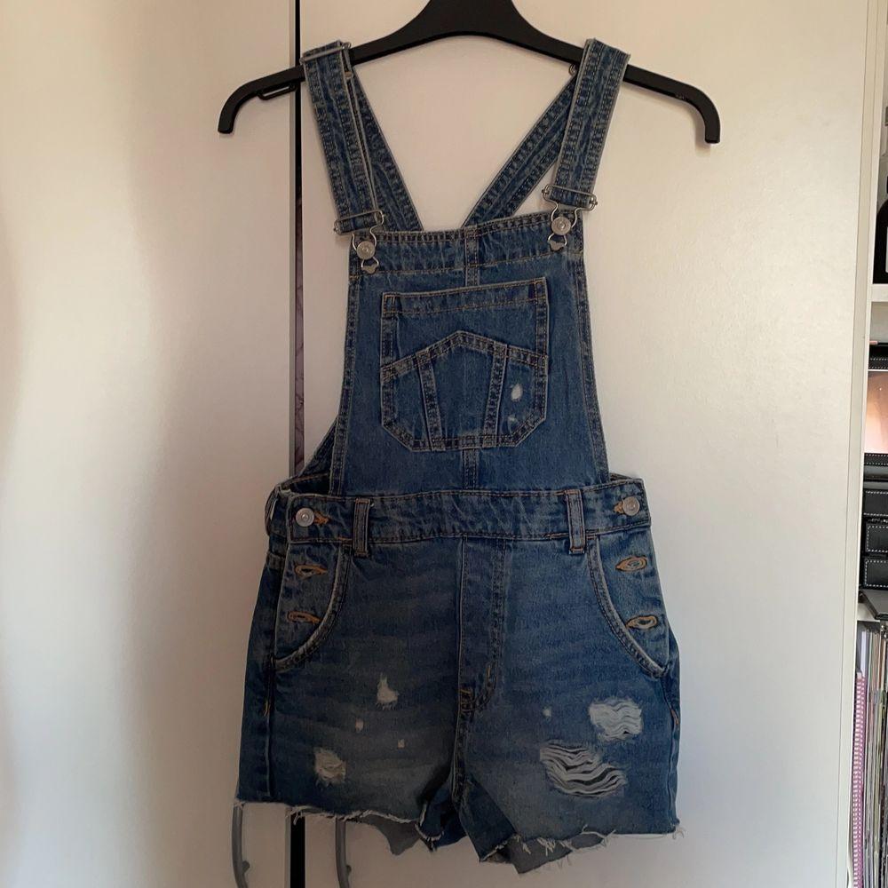 Hängselbyxor (short) i jeans material. Skit snygg inför sommaren. Säljs pga av att den är för liten. Helt oanvänd dock.. Jeans & Byxor.