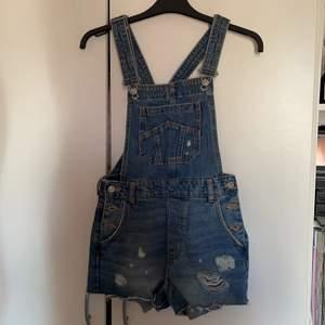 Hängselbyxor (short) i jeans material. Skit snygg inför sommaren. Säljs pga av att den är för liten. Helt oanvänd dock.