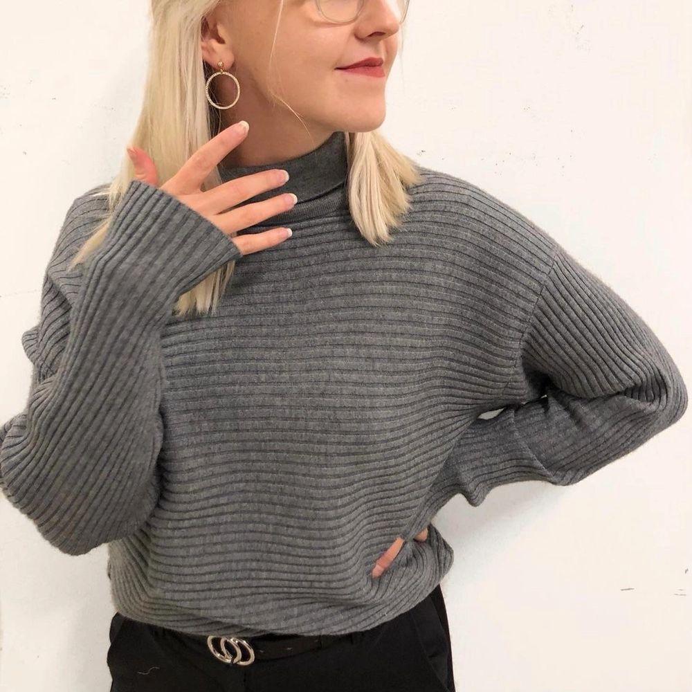 Mörkgrå ribbad stickad tröja med lite polokrage. Supersjuk och skön i materialet. Aldrig använd. Fler bilder kan tas vid önskemål. Frakt tillkommer.. Stickat.