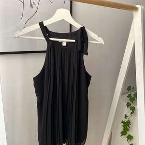 Classy svart linne med knytning vid axeln och plisserad framsida. Helt ny och oanvänd 🤍 köparen står för frakten ✨