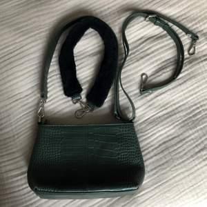Säljer min mörkgröna handväska från Rizzo!! Det medföljer ett längre skinnband och ett i fakepäls. Använd sparsamt