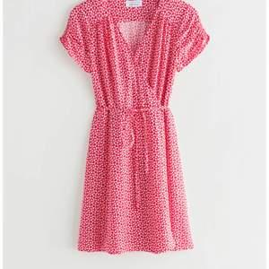 Röd mini-dress i omlottstil med vita blommor på röd botten❤️En älskad klänning som tyvärr krympt i tvätten. Köpte den i strl 34 o kan tänka mig att den passar XXS-XS. Köparen står för frakt