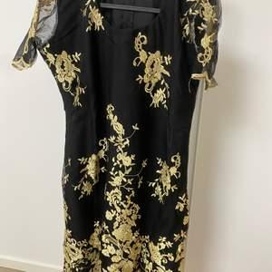 Jättebra svart med gul blommor oanvänd designer klänning, lång 40, storlek 40.