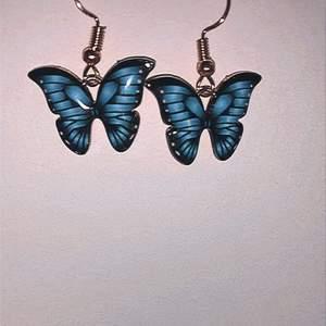 Kort söta blåa fjäril örhänge med svart detaljer. I ny och fin skick. Kan fraktas eller mötas upp💙