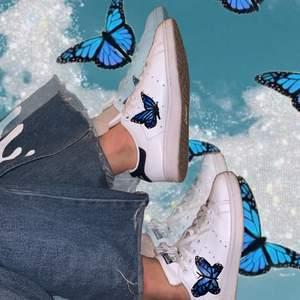 🦋 Ett par vita stan smiths med svarta detaljer. Jag har målat fjärilarna på dem själv med vattentät läderfärg. De är i förvånansvärt bra skick men ej sprillans nya🥰 supper trendiga och matchar till allt✨🦋