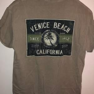 Beige/grå T-shirt med Venice Beach tryck. Litet tryck på höger framsida och stort tryck på ryggen. Uppvikta ärmar