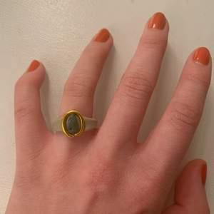 En ring av beige lera med guldig ståltråd och en liten grön kristall! Kristallen är äkta, det är grön aventurin!✨