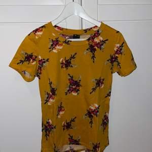 Säljer denna T-shirt jag köpte från ginatricot för några år sedan använt den 1 gång inte mer än det, den är jättefin och otroligt skön är senapsgul med fina blommor på, passar perfekt till sommaren