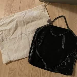 Stella McCartney Bag Svart Falabella kedjetrimmad tote väska från STELLA MCCARTNEY med kedjelänk, magnetfäste, logotyp charm, invändig ficka med dragkedja och foder med logotryck.