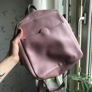Jättefin rosa ryggsäck i läder med många fack. Lite sliten.