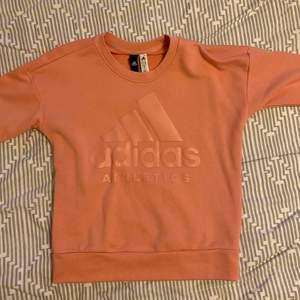 Adidas sweatshirt i storlek S men är lite oversize så om man har strl M så passar den. färg: peach, skick: tröjan är i jätte bra skick är helt ny. Har enbart använts en gång då strl var för liten. Kan mötas upp i Göteborg annars tillkommer frakt. OBS: pris kan diskuteras vid snabb och seriös köp