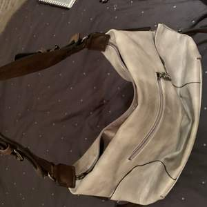 Ganska stor grå läderväska med bruna läderband och detaljer.