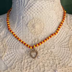 Ett eget pärlat halsband med ett hjärta i mitten! Varannan gul pärla och varannan röd pärla. Ett silvrigt knäppe där bak. Halsbandet är 41 cm lång!❤️                                                 Hjärtat återanvände jag från ett gammalt halsband som gott sönder. Och pärlorna kommer också från ett gammalt halsband.                                                                                    Halsbandet är gjort av fiskelina och ska vara mycket stabilt! Skriv privat vid inträde.