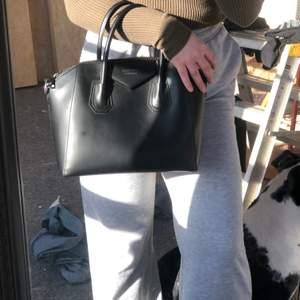 Handväska med axelremmar som medföljer.