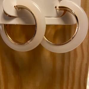 Stora örhängen i vit med snygga metalldetaljer. ( guld) priset inkl frakten