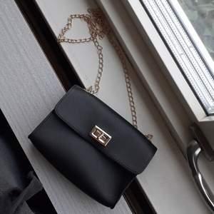 En svart liten handväska med
