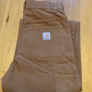 """Vida byxor från carhartt med snygga detaljer på sidorna som är helt oanvända men lappen är borta, är i färg """"carhartt brown 210, storlek 16(år) men passar bra på mig som är 36/38 och 170 cm."""