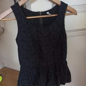 Säljer en svart topp med volangliknande nederdel. Full med små hål som detaljer och därför lite *genomskinlig