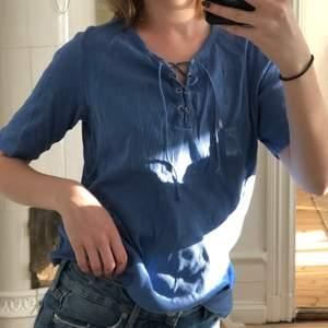 Ljusblå t-shirt i ribbat material med knytning framtill💙