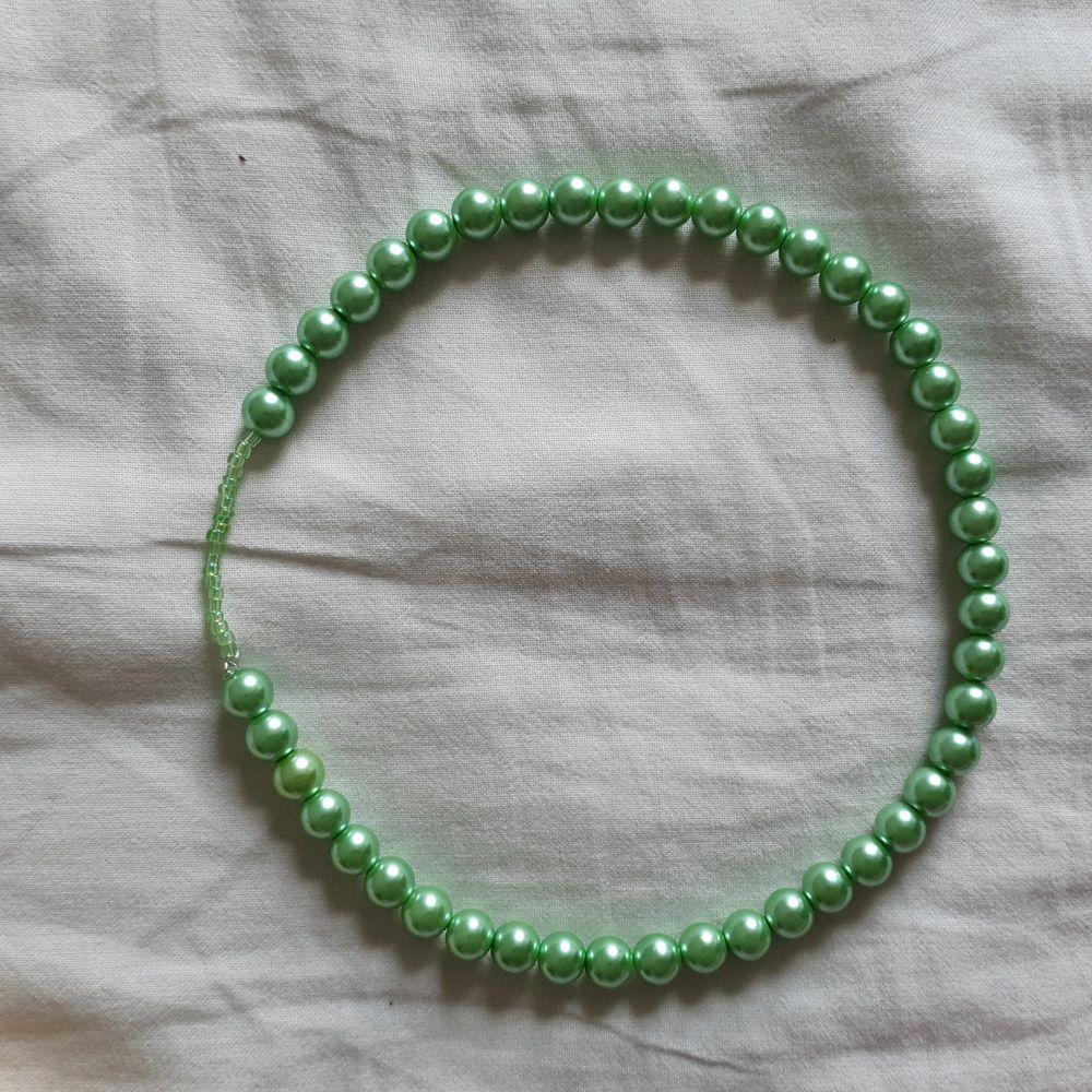 Ett egengjort grönt pärlhalsband med elastiskt band🍀OBS halsbandet med blomman är inte till salu. DM vid frågor💚 Står ej för frakt. KOLLA IN PROFIL FÖR FLER SAKER😊. Accessoarer.