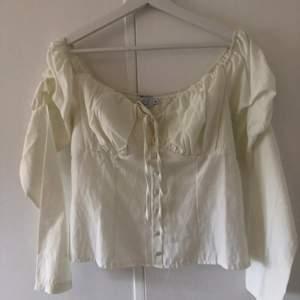 En vit sommarblus från nakd i storlek 38🧡superfin då man kan ha den både på axlarna eller off shoulder, aldrig använd!