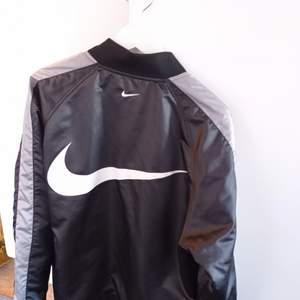 Nike Sportswear Swoosh Woven Bomber Jacket (Unisex)  Vårjacka unisex strl s/m. Nytvättad utan några som helst täcken på användning. Avhämtning eller postnord. Överföring till Swedbank eller kontant. Ej swish!