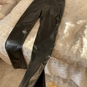 Ett par ganska bekväma svarta skinbyxor som blir lite wide vid botten där det också finns en slit. Aldrig använda.