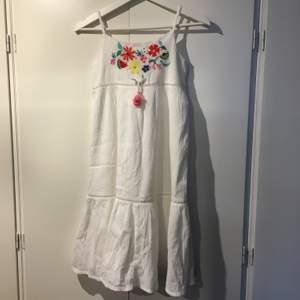 Vit klänning med dekorationer. I väldigt bra skick. Storlek 134 men passar som storlek S. Kommer från H&M. Frakten ingår inte