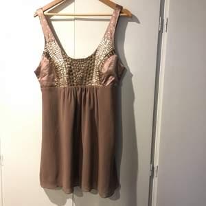 En ljus beige klänning strl 46. Kommer från Joy of Love. Är i en ljusare färg än den i bilden. Frakt ej inkluderat