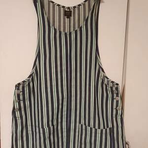 En söt klänning från Pop London i ett tunnare denimtyg. Den har knappar i sidorna och på armarna samt två fickor framtill. Den är använd men i mycket gott skick. Det står storlek 4. Jag är en small-medium och på mej är den rymlig så passar nog M-L bra med.