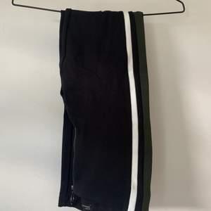 Byxor/tights från Zara. Svarta med grönt och vitt streck på vardera sida samt en dragkedja fram. Storlek 36/S. Köparen står för frakt.