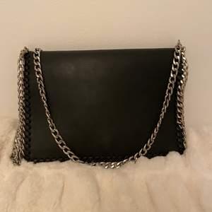 En liten kuvertväska från Nelly i svart fejkläder. Sparsamt använd med en silverkedja.