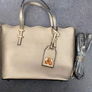 Säljer en helt ny handväska i brons/guld färg. Superfin och rymmer mycket. Den är oanvänd med prislapp på och inplastad. Pris 150kr