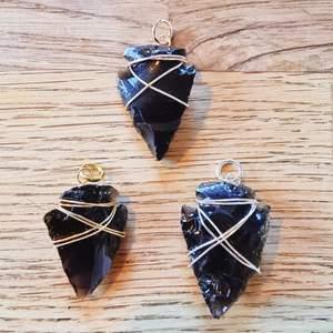Pilspets-format hängsmycke av svart obsidian. Cirka 3-4 cm långt.   Går att få i färgerna: silver, guld och rose. Färg och form på kristallen kan variera lite då det är en naturlig sten, och formen är huggen för hand.   Skickas i vadderat kuvert via postnord.