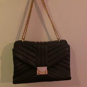 Väska med gulddetaljer, superfint skick och väldigt rymlig! Kan ha över axeln eller runt kroppen, justerbar kedja 🤍