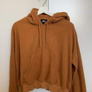 Superfin brun hoodie från Stussy i lite fleece material. Lite kortare modell och superskön! Strl s nypris 1300kr. Jättebra skick.