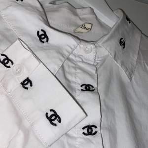 En vit skjorta med chanel mönster på sig. Vet inte vad storleken är men gissar mellan s-m. Tror det kan bli trångt om man har större byst. Passar till de mesta och är gjort av ett tunt material. Den har en mindre fläck på sig på baksidan. Den har legat i en kartong och är i ett desperat behov av att bli struken haha