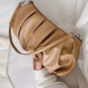 Brun liten veckad väska med kort band. Väskan är från shein och är aldrig använd. Frakt tillkommer!