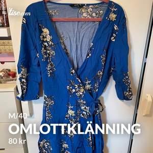 Blå klänning med blommor och vita revärer på armarna! Omlottklänning, så är anpassningsbar i storlek.