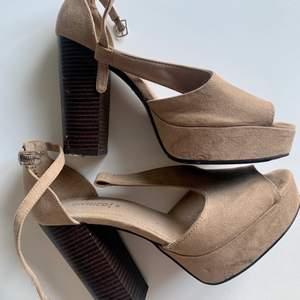 Beiga mocka klackskor med tjock mörk träklack. Skorna har rem vid fotleden som kan justeras, storlek 39, klackens höjd: 12 cm. skicket är använt och små skavanker finns (se bilder)